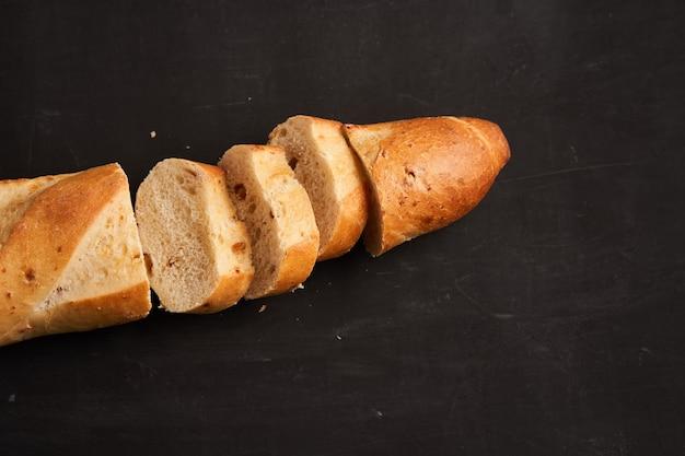 Uma baguete francesa crocante fatiada encontra-se preta escura com fundo de mesa sementes de gergelim.