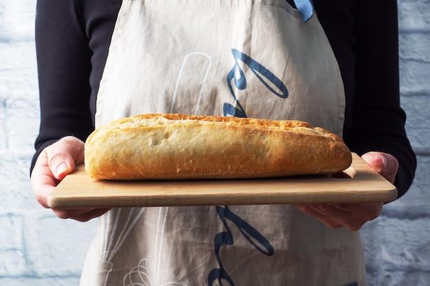 Uma baguete fresca de pão em uma placa de madeira está nas mãos de uma chef feminina.
