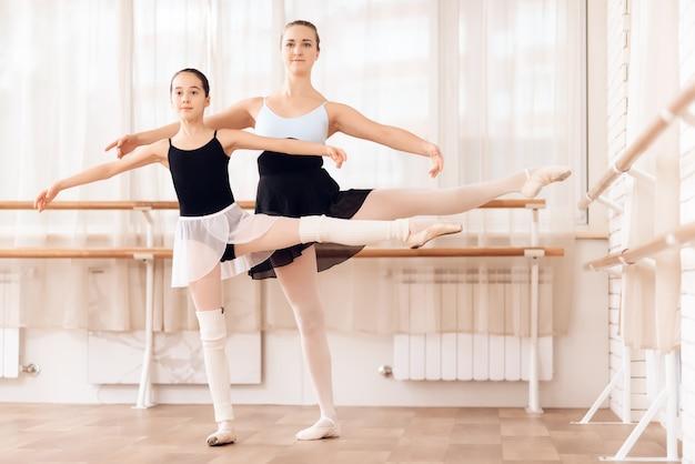 Uma bailarina adulta e uma bailarina estão dançando no ginásio.