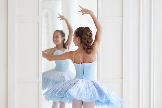 Uma bailarina bonita em traje de balé e na ponta dança perto do espelho. garota na aula de dança. a menina está estudando balé. bailarina está dançando. a dançarina está treinando no espelho.