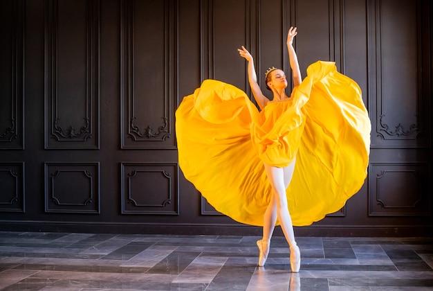 Uma bailarina elegante em sapatilhas de ponta dança com um tecido amarelo esvoaçante sobre um fundo cinza escuro