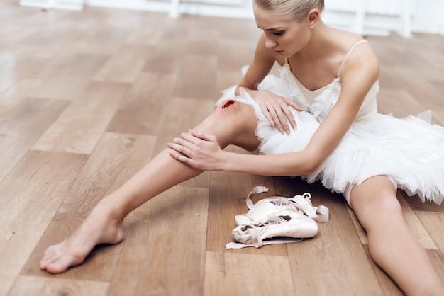 Uma bailarina profissional está sentada no chão.