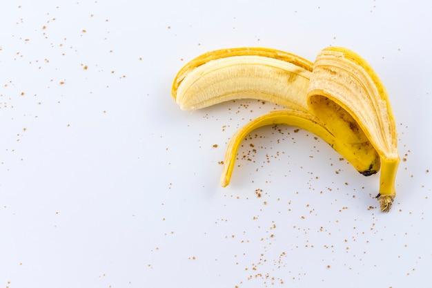 Uma banana descascada na mão de uma mulher em branco