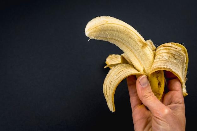Uma banana descascada na mão de uma mulher no preto