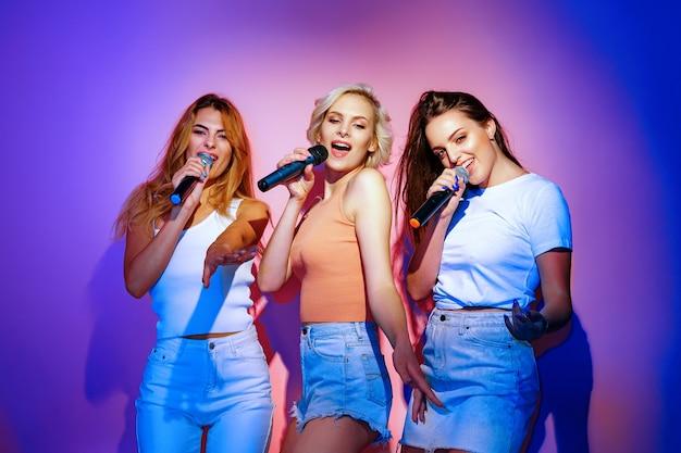 Uma banda sorridente de jovens garotas cantando músicas no microfone