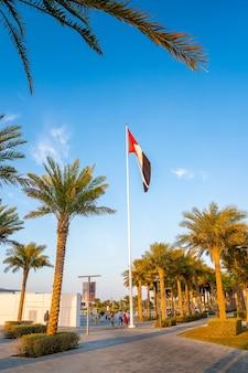 Uma bandeira dos emirados árabes unidos tremulando contra um céu limpo e tranquilo.