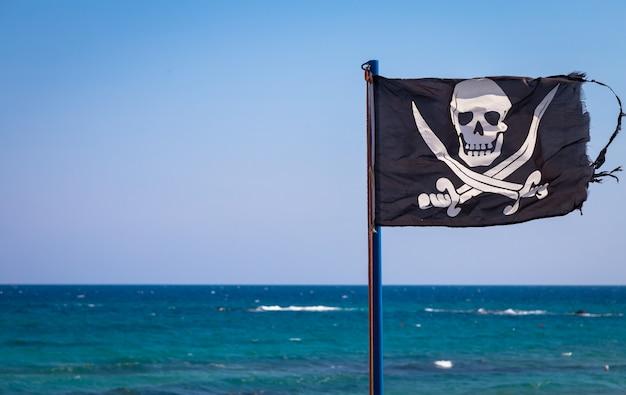 Uma bandeira pirata danificada durante um dia de forte vento, com copyspace