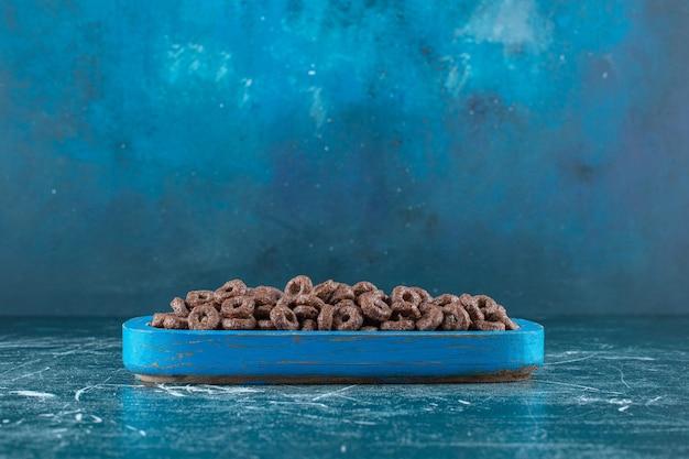 Uma bandeja com anéis de milho, na mesa azul.