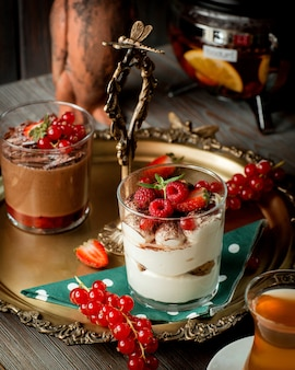 Uma bandeja com dois copos de tiramisu e pudim de chocolate decorado com frutas.