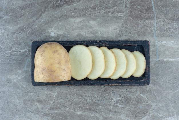 Uma bandeja com fatias de batata, sobre a mesa de mármore.