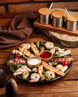 Uma bandeja com vista de cima com refeições de carne e peixe junto com diferentes molhos na mesa de madeira marrom.