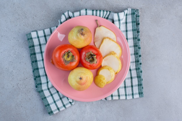 Uma bandeja de frutas com peras e caquis em uma toalha, sobre fundo de mármore.