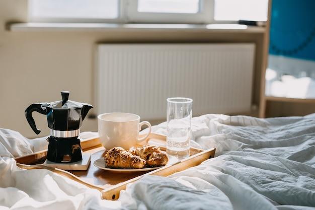 Uma bandeja de madeira com croissants e xícara de café na cama