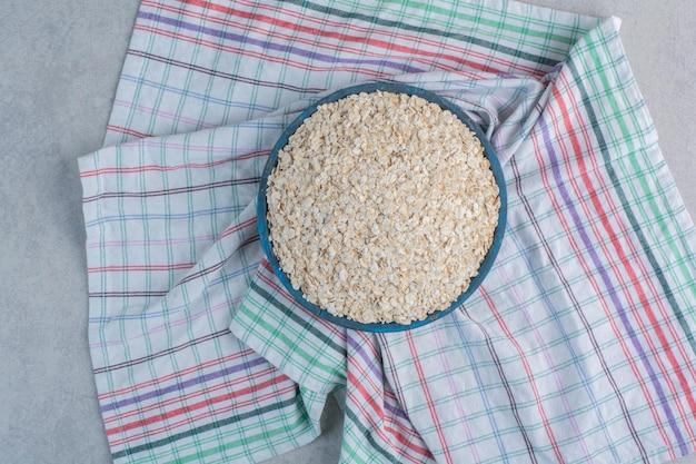 Uma bandeja redonda cheia de flocos em uma toalha na superfície de mármore