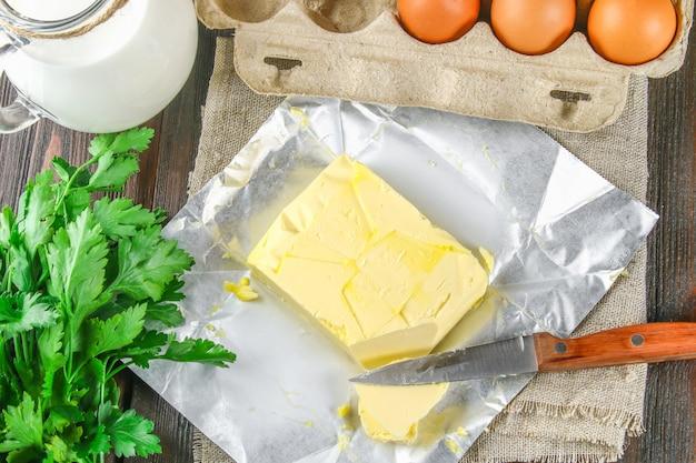 Uma barra de manteiga é cortada em pedaços em uma placa de madeira com uma faca