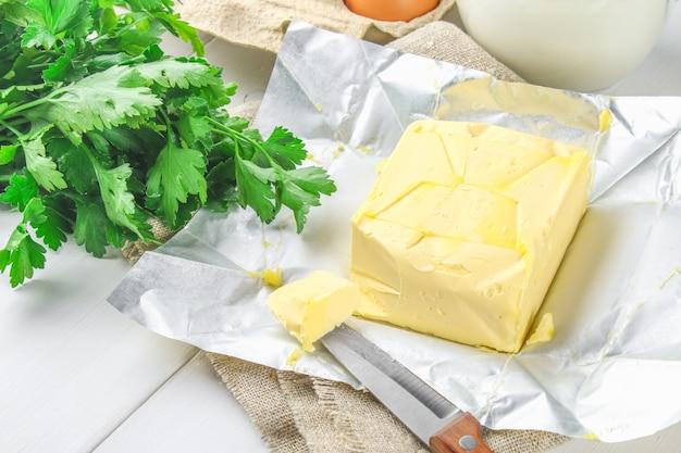 Uma barra de manteiga é cortada em pedaços em uma placa de madeira