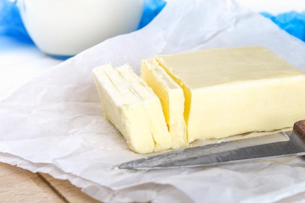 Uma barra de manteiga em uma placa de madeira com uma faca, sobre uma mesa branca. ingredientes para cozinhar