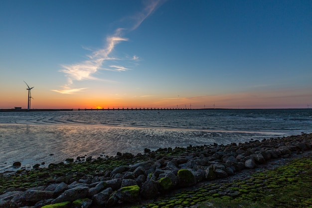 Uma barreira de tempestade e moinhos de vento na província de zeeland, na holanda, ao pôr do sol