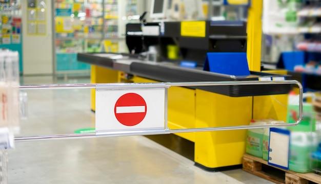 Uma barreira fechada, sinal de pare no supermercado de mercearia de alimentos, terminal de caixa temporariamente fechado