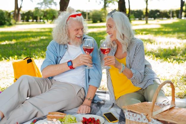 Uma bebida agradável. casal feliz e feliz bebendo vinho enquanto faziam um piquenique