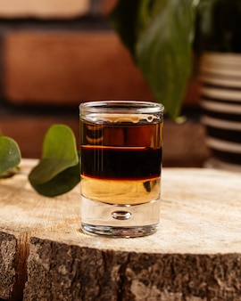 Uma bebida alcoólica de vista frontal dentro de um copo na mesa de madeira marrom