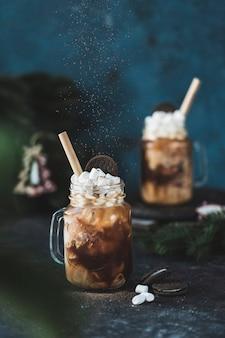 Uma bebida de café gelado com gelo e leite em um copo com marshmallows e biscoitos em um fundo escuro com galhos de árvores de natal.