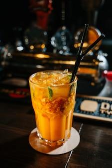 Uma bebida de laranja em um copo com cubos de gelo, folhas de laranja, palha e hortelã