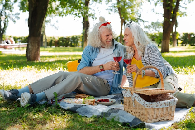 Uma bebida deliciosa. casal alegre e simpático curtindo a esposa enquanto faz um piquenique no parque