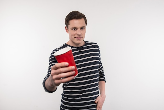 Uma bebida deliciosa. homem alegre e simpático sorrindo enquanto mostra uma xícara de café