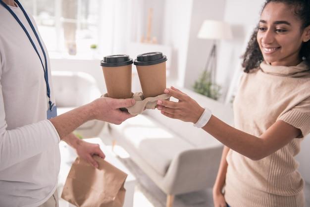 Uma bebida deliciosa. perto de xícaras com café sendo oferecido a uma jovem alegre