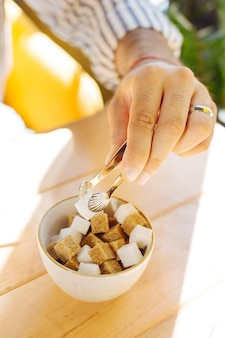 Uma bebida doce. vista superior do açúcar sendo adicionado ao café enquanto o torna doce