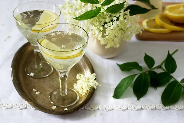 Uma bebida fresca com limão e xarope de sabugueiro em copos em uma bandeja de metal. estilo rústico.