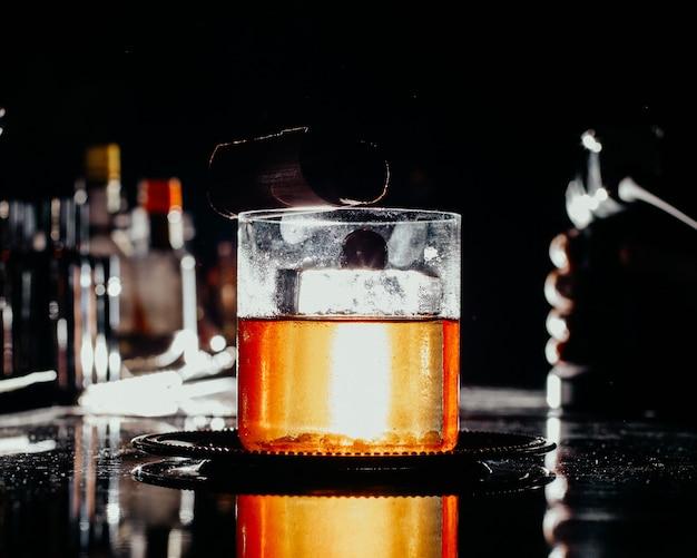 Uma bebida gelada com vista frontal dentro de um pequeno copo na mesa escura do bar.