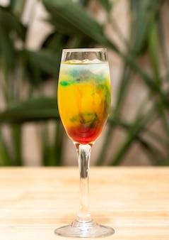 Uma bebida preparada com licores coloridos em um copo alto com gelo sobre uma mesa de madeira