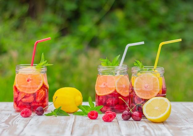 Uma bebida refrescante à base de limão, frutas vermelhas e hortelã. água de desintoxicação. coquetel de frutas cítricas de verão.
