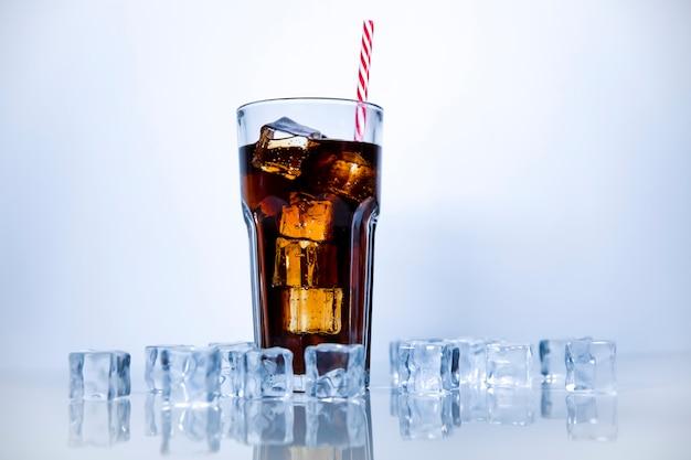 Uma bebida refrescante de estaca é derramada em um copo de vidro com um tubo. fundo branco com cubos de gelo espalhados.