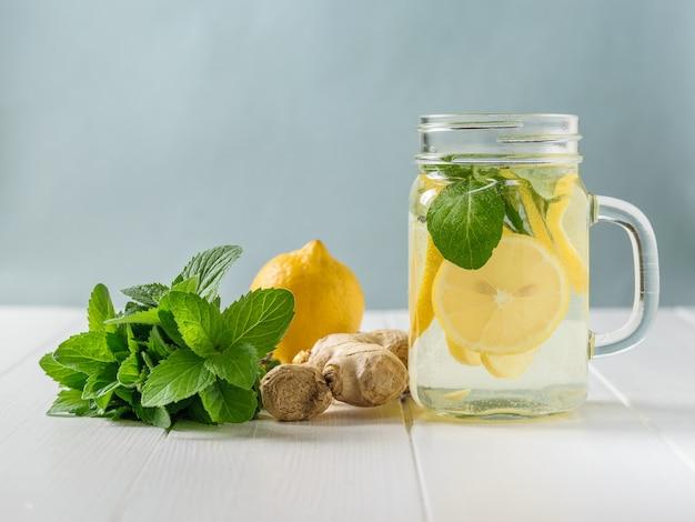 Uma bebida refrescante de limão, hortelã e fatias de raiz de gengibre em uma mesa de madeira branca.