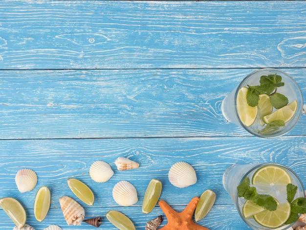Uma bebida refrescante de verão com limão e hortelã mojito fica em placas azuis com conchas e estrelas do mar. vista superior, copie o espaço.