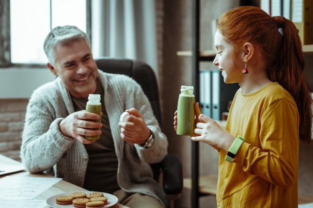 Uma bebida saborosa. menina alegre e feliz segurando uma garrafa com suco enquanto bebe com o pai