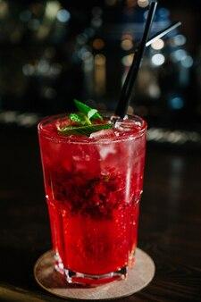 Uma bebida vermelha em um copo com cubos de gelo, morangos, palha e folhas de hortelã