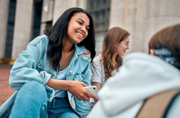 Uma bela aluna afro-americana se senta com amigos nos degraus perto do campus e se comunica.