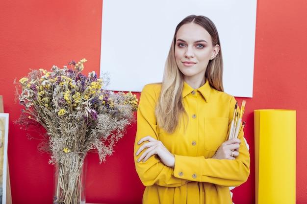 Uma bela artista. uma bela jovem artista de olhos azuis usando um vestido amarelo em pé perto de uma parede vermelha
