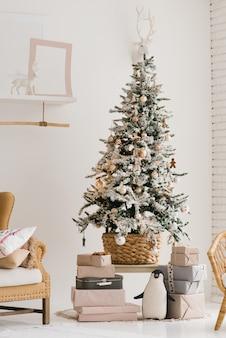 Uma bela árvore de natal com neve artificial fica na sala de estar em cores bege e claras