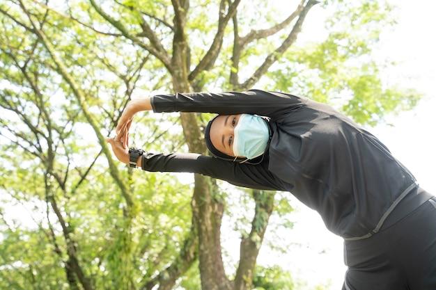 Uma bela atleta muçulmana se alongando e exercitando seu corpo ao ar livre e usando máscara facial para proteção contra vírus