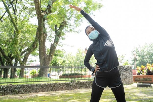 Uma bela atleta muçulmana se alongando e exercitando seu corpo ao ar livre e usando uma máscara facial para proteção contra vírus