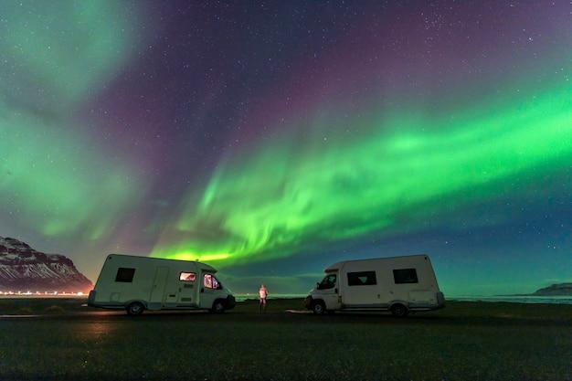 Uma bela aurora verde e vermelha dançando sobre a lagoa de jokulsarlon, islândia