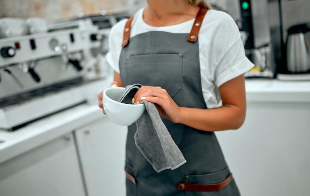 Uma bela barista vestida com um avental lava uma xícara com um pano atrás do balcão em uma cafeteria.