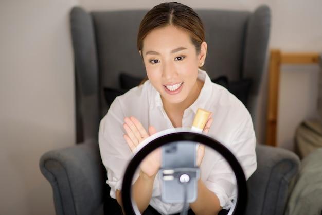 Uma bela blogueira de maquiagem asiática está transmitindo ao vivo como fazer a maquiagem do rosto de beleza em sua casa, conceito de beleza e tecnologia