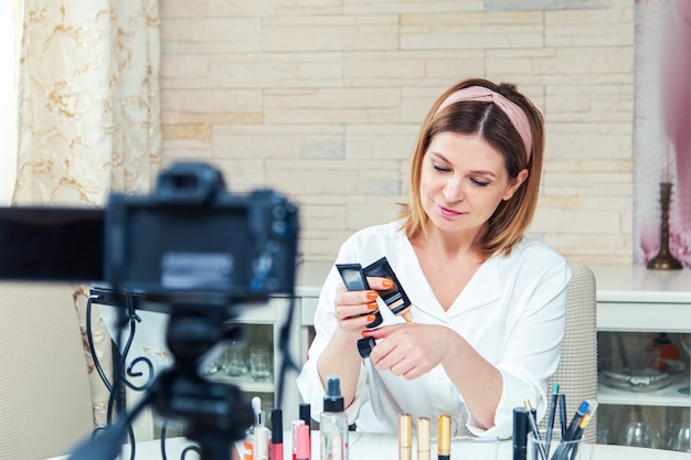 Uma bela blogueira de meia-idade mostra como usar cosméticos. gravação de blog de vídeo ao vivo em casa. a versão moderna do trabalho em casa.