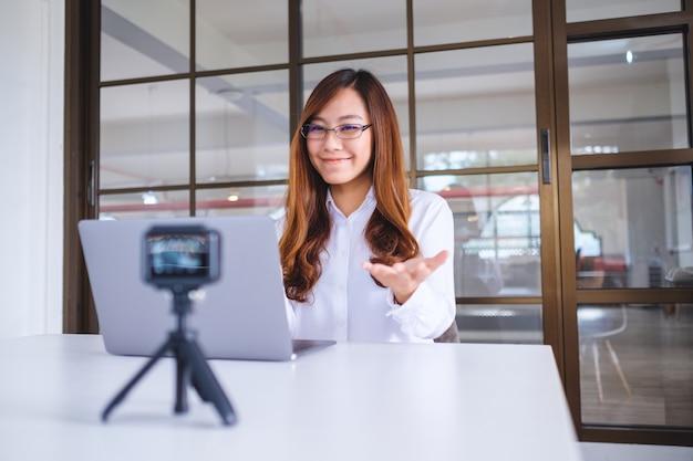 Uma bela blogueira ou vlogger asiática gravando um vídeo